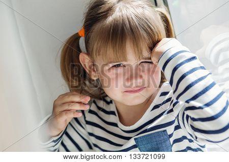 portrait of a little girl upset window