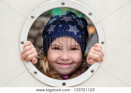 Happy little girl playing hide and seek outdoors