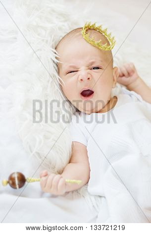 Portrait of a newborn baby boy with a golden crown