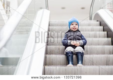 Cute little child sitting on moving staircase in shop