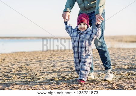 happy baby learning to walk on the sand