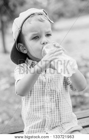 cute toddler boy drinking water outdoors ( black and white )