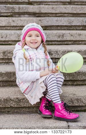 happy little girl with a balloon sitting on the steps