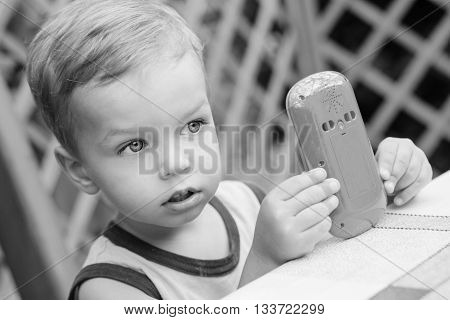 portrait of cute little boy playing with a toy telephone ( black and white )