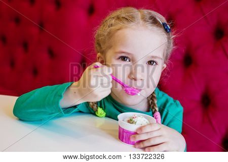 little girl eating ice cream in a cafe from the cup