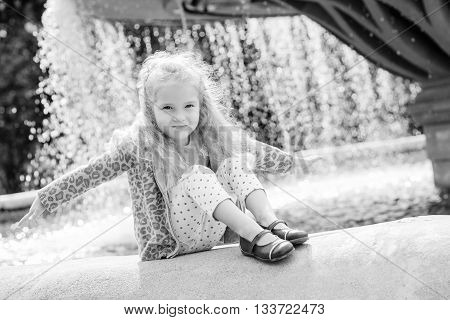 Cute little girl playing with a city fountain a sunny day ( black and white )
