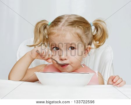 happy little girl eats with a spoon while sitting at table on white background