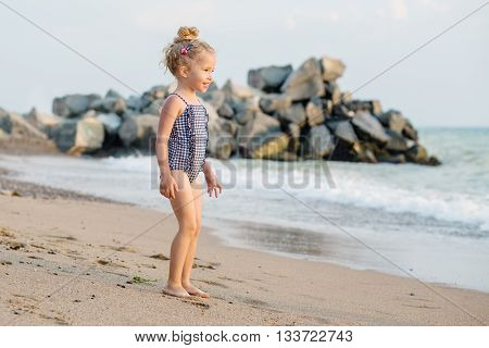 Portrait of a happy charming little girl on the beach