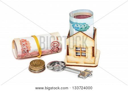 Wooden house Russian money and key on a white background. Housing costs