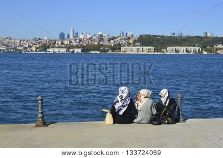 Istanbul Turkey - October 20 2013: Sea of Marmara the Bosphorus. Middle East three women sitting on the beach looking at the sea resting.