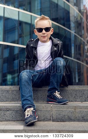 baby boy 7 - 8 years in sunglasses and black leather jacket smiling on the background of the glass building in the summer, in warm weather