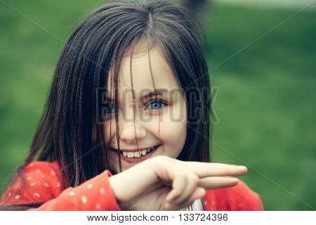 Smiling face of little cute happy girl child with blue eyes and brunette hair outdoor closeup on blurred green background