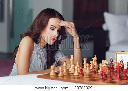 Woman playing chess indoor and thinking position find winning move strategy