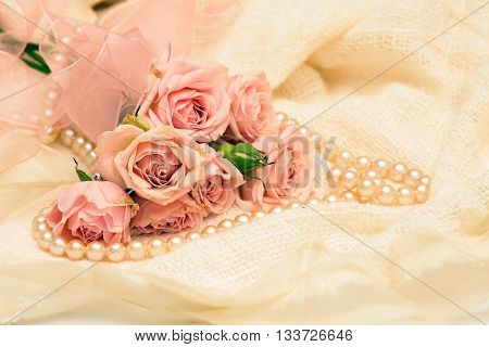 roses and pearls on the background of delicate lace and white fabric