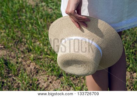 girl walking in the green field in a white short dress and holds in her right hand a straw hat. shot in motion on the model