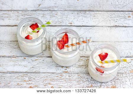 Three in a jar of yogurt with strawberries on a wooden board