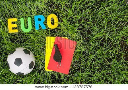 Euro football championship - image with ball, referee yellow, red card on green lawn. Symbol of soccer and fair play. Empty space for text.