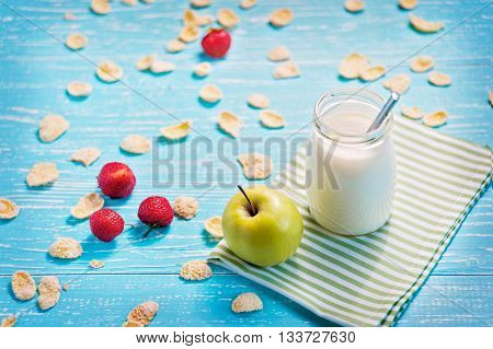 Jar of milk and green apple in the striped napkin on the table. Corn flakes with strawberry scatter.
