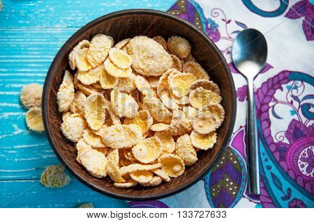 cornflake cereal in bowl with spoon on table with napkin top view closeup