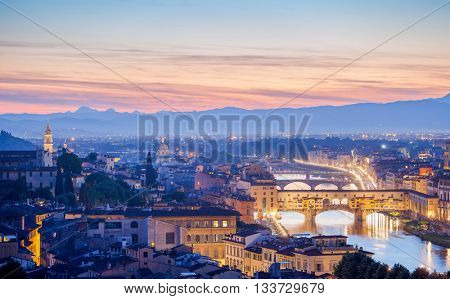 Bridges the arno river florence italy old town in late evening sunset with illumination lights through smoke of mist
