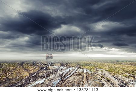 Dirty rural road with puddles and mud under dark dramatic stormy sky SUV car goes far away transportation background