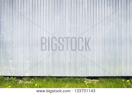 Corrugated Metal Fence Stands On Green Grass