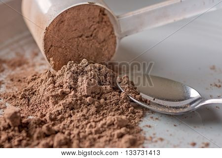 Chocolate meal replacement powder pouring from a scoop with a spoon next to it