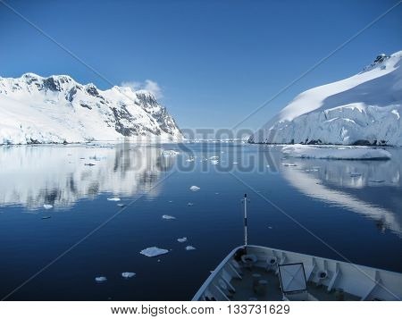 Stunning Antarctic landscape of the Lemaire Channel with its clear blue waters reflecting the snowy mountains.