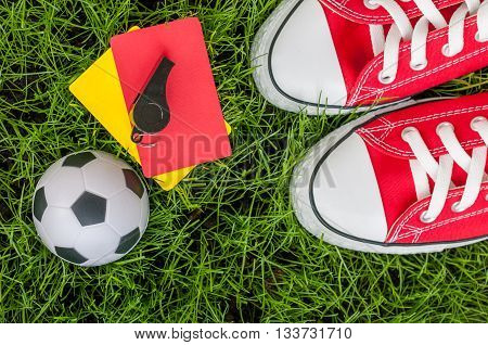 Soccer players outfit on green field or lawn of stadium with referee red yellow card and football ball.