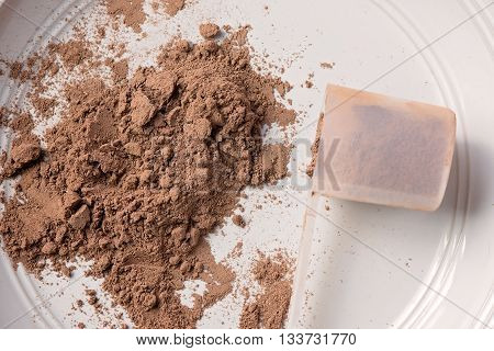 Chocolate meal replacement powder on a plate with a scoop