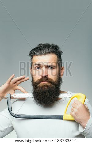 handsome young man with long dark haired beard and moustache cutting with sharp tool of saw on grey background