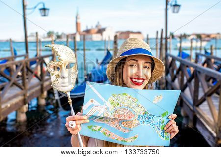 Young smiling woman traveling with paper map and venetian mask standing near San Marco square with gondolas on the background in Venice.