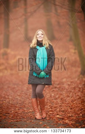 Autumn time concept leisure. Girl is walking through the park. Young woman speanding free time outside enjoying good autumnal weather.