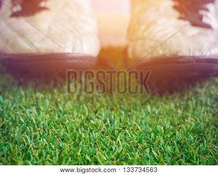Artificial Grass With Blurry Background Of Old Muddy Dirty Football Shoes With Copy Space