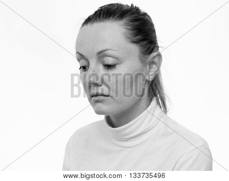 Emotions. Close up portrait of a sad woman looking down isolated on white background black and white