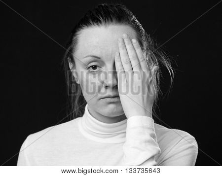 Close up portrait of a woman closing half of her face by the palm dark background black and white