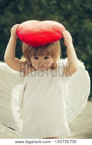 small cute baby boy with blonde long hair in white feathered angel wings and cloth holding red heart pillow outdoor on green natural background