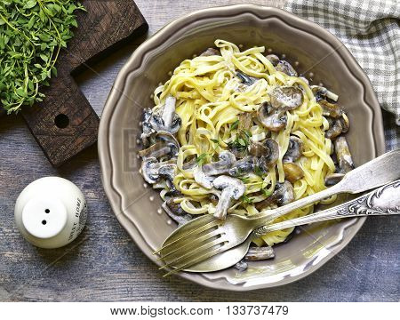 Tagliatelle with mushrooms and thyme in a cream sauce.Rustic style.