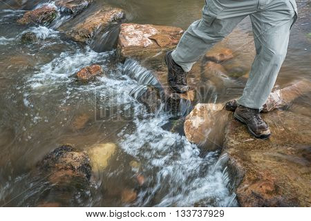 legs of a male hiker crossing mountain creek in Colorado foothills