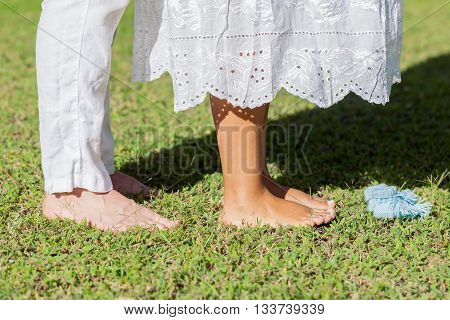 Young Pregnant Couple Feet With Newborn Baby Booties In Nature