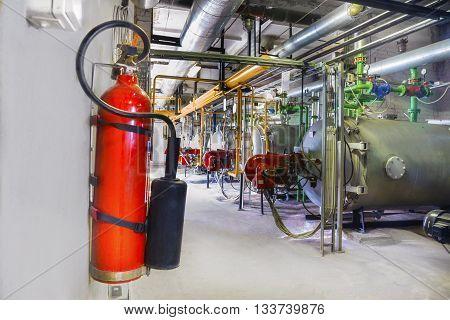 Old gas steel boilers and fire extinguisher on a wall established in old boiler-house