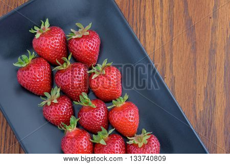Strawberries with stems on a black platter