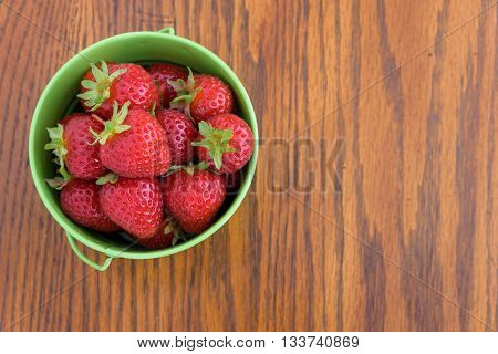 Strawberries with stems in a green bucket