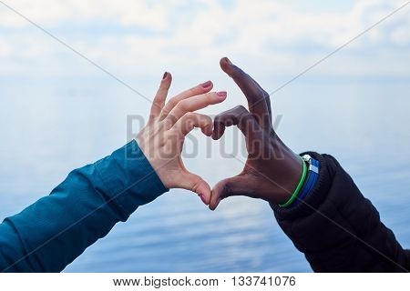 Interational love.White and black hands make heart symbol