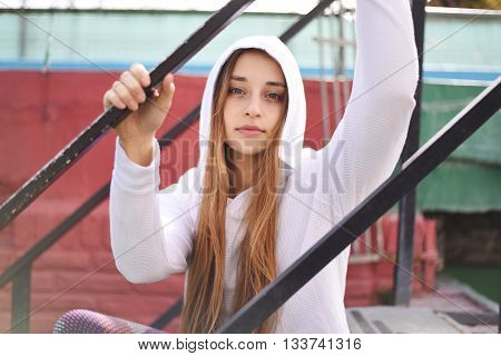 Portrait of an attractive young woman with sport clothes sitting at stairs.
