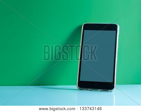 still life shot on smart phone touch screen mobile phone on green background