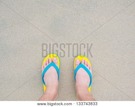 human bare feet standing on the flip-flop sandal footware on the sea beach