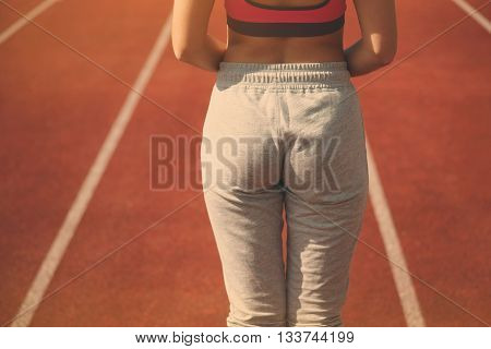 Female athlete buttocks and running track on the background