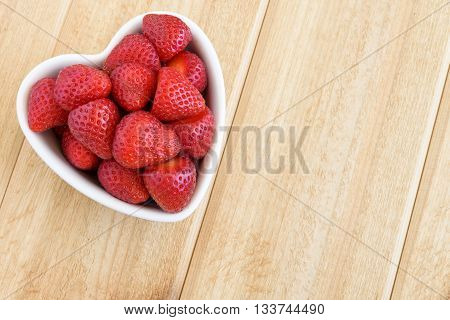 Whole strawberries in a white heart shaped bowl