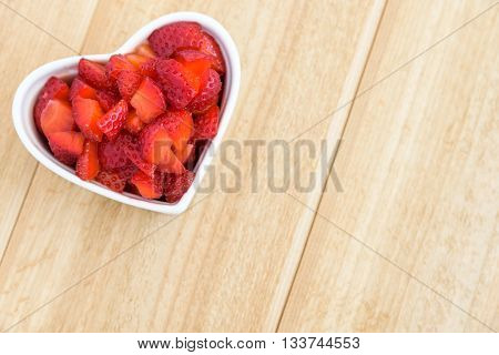 Diced strawberries in a white heart shaped bowl